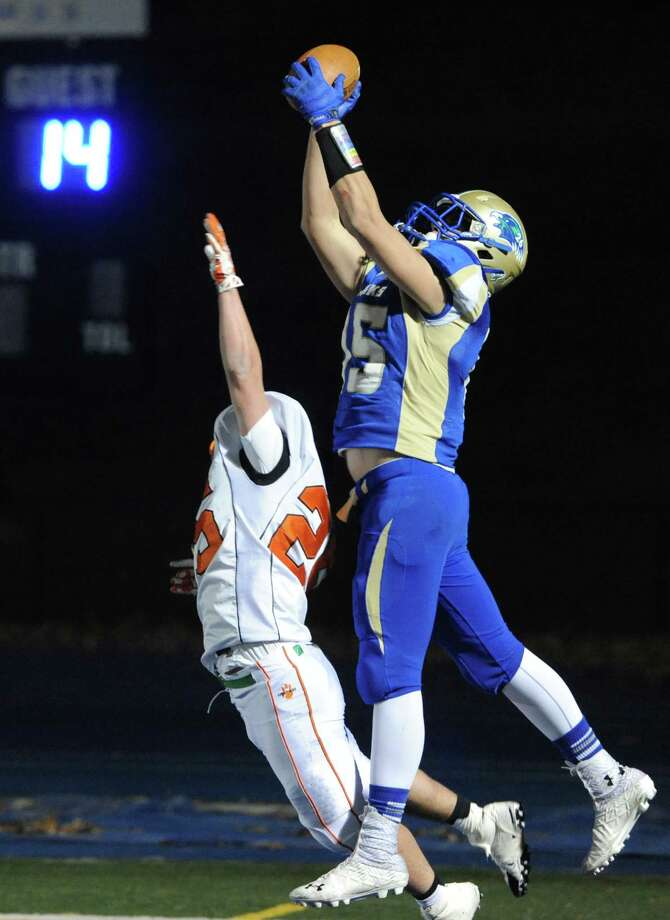 Newtown wide receiver Julian Dunn, right, catches a touchdown over Ridgefield defensive back Aidan Mauro in the CIAC Class LL state quarterfinal football game between Ridgefield and Newtown at Newtown High School in Newtown, Conn. on Tuesday, Dec. 3, 2013. Photo: Tyler Sizemore / The News-Times