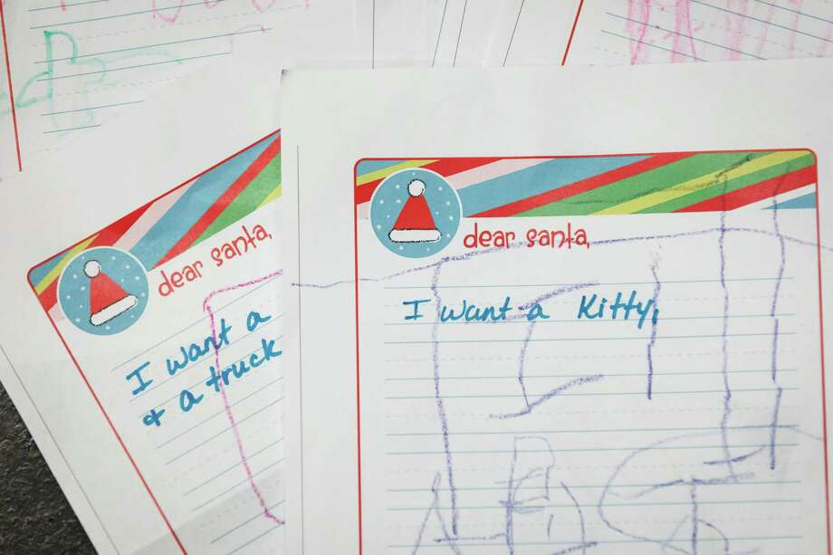 Holiday wish list letters written by 3-5 year-old students from The Children's University Inc. after visiting Santa at the Pasadena Post Office, Tuesday, Dec. 3, 2013, in Pasadena. Photo: Michael Paulsen, Houston Chronicle / © 2013 Houston Chronicle