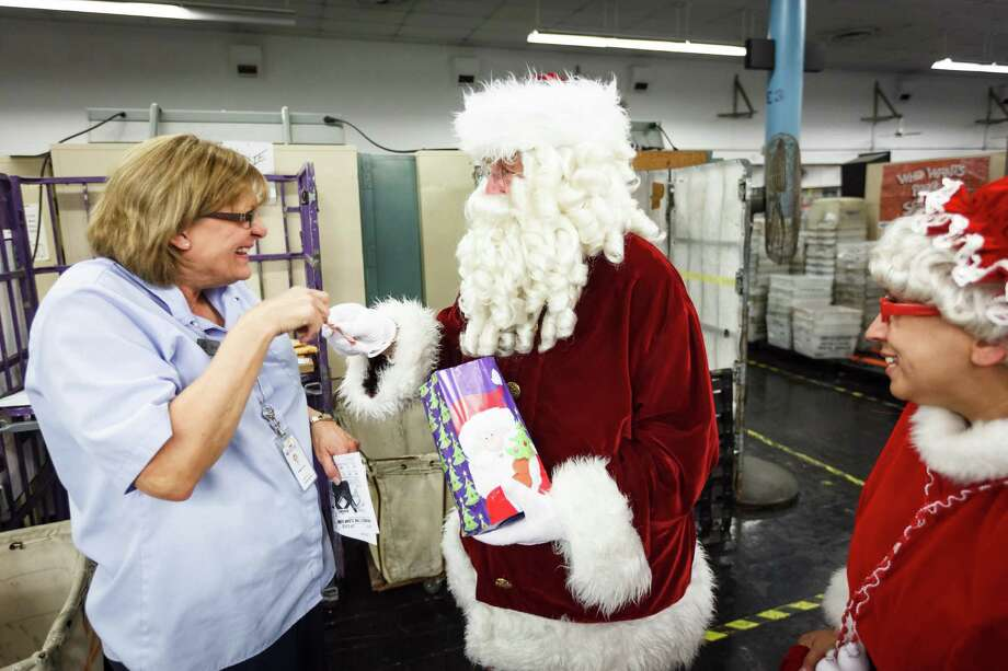 Teena Mouser reacts after meeting Santa and Mrs. Claus as he takes a break in the Pasadena Post Office mail sorting room after taking holiday wish list letters from The Children's University Inc. students, Tuesday, Dec. 3, 2013, in Pasadena. Photo: Michael Paulsen, Houston Chronicle / © 2013 Houston Chronicle