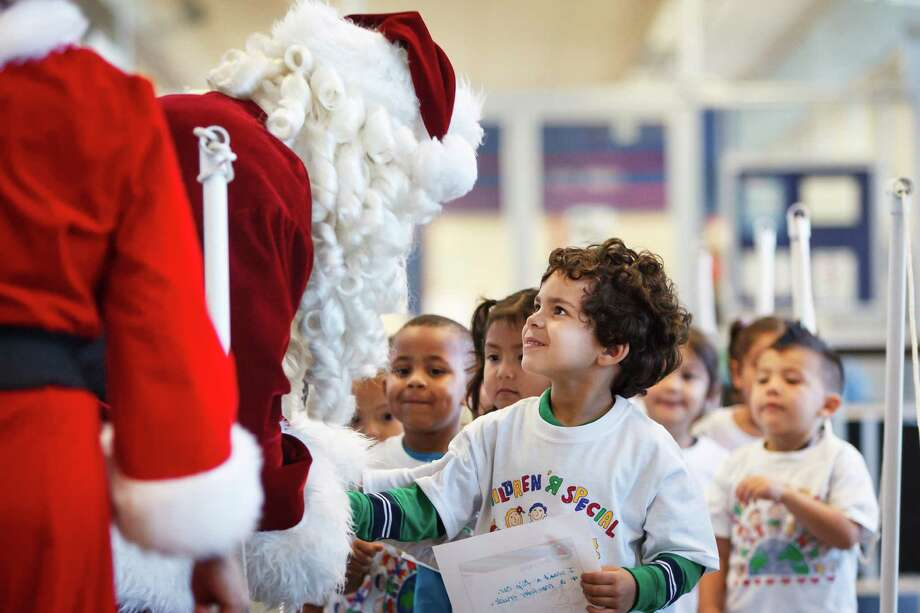 Bruce Lee III, 4, talks to Santa and Mrs. Claus as he and other students from The Children's University Inc. share their holiday wish lists at the Pasadena Post Office, Tuesday, Dec. 3, 2013, in Pasadena. Photo: Michael Paulsen, Houston Chronicle / © 2013 Houston Chronicle