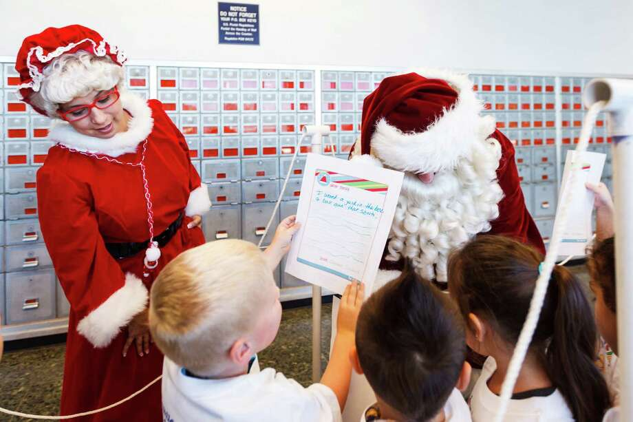 Connor Seward, 4, shows his holiday wish list letter to Santa and Mrs. Claus as he and other students from The Children's University Inc. visit Santa at the Pasadena Post Office, Tuesday, Dec. 3, 2013, in Pasadena. Photo: Michael Paulsen, Houston Chronicle / © 2013 Houston Chronicle