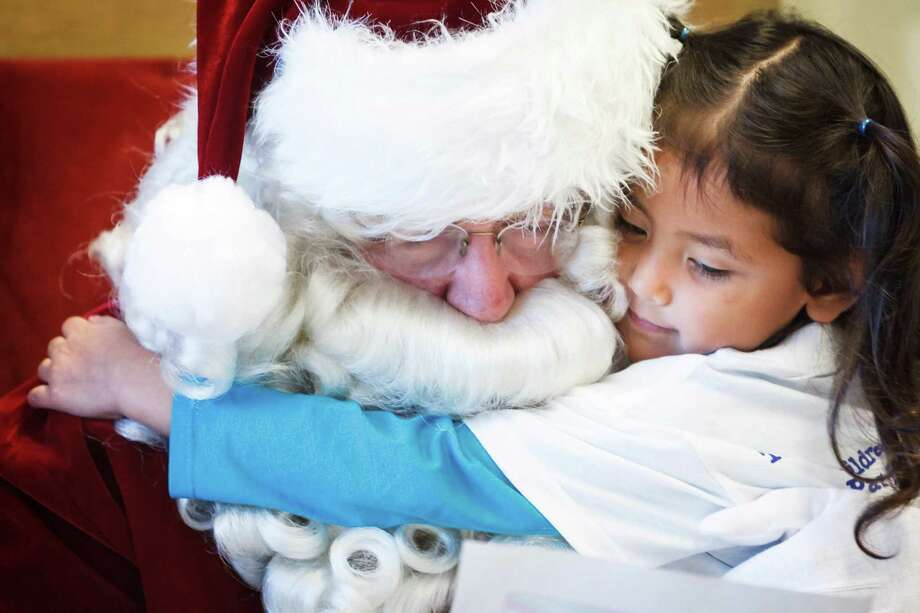 Ava Moreno, 3, gets a hug from Santa as he reads her holiday wish list letter as she and other students from The Children's University Inc. visit Santa at the Pasadena Post Office, Tuesday, Dec. 3, 2013, in Pasadena. Photo: Michael Paulsen, Houston Chronicle / © 2013 Houston Chronicle
