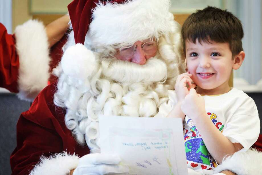 Aydan Guzman, 4, sits on Santa's lap as he and other students from The Children's University Inc. visit Santa and share their holiday wish list letters at the Pasadena Post Office, Tuesday, Dec. 3, 2013, in Pasadena. Photo: Michael Paulsen, Houston Chronicle / © 2013 Houston Chronicle
