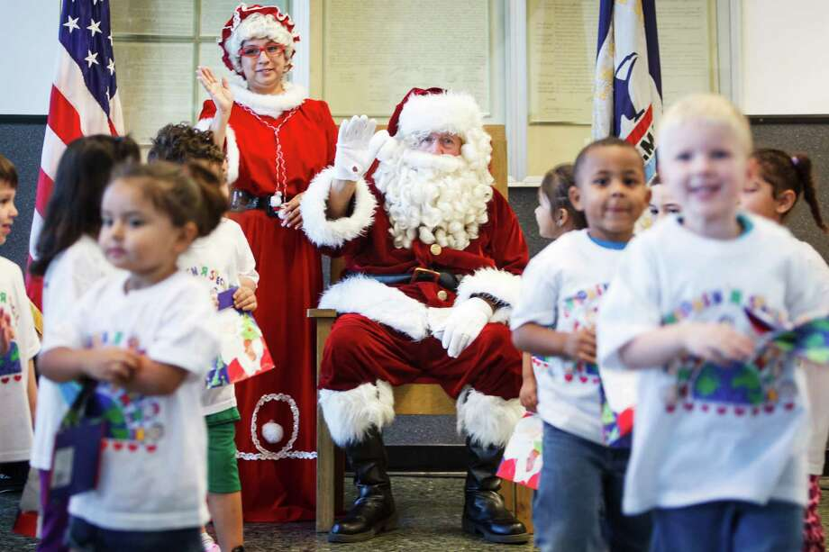 Santa and Mrs. Claus waive goodbye to students from The Children's University Inc. who visited the Pasadena Post Office to share their holiday wish list letters, Tuesday, Dec. 3, 2013, in Pasadena. Photo: Michael Paulsen, Houston Chronicle / © 2013 Houston Chronicle