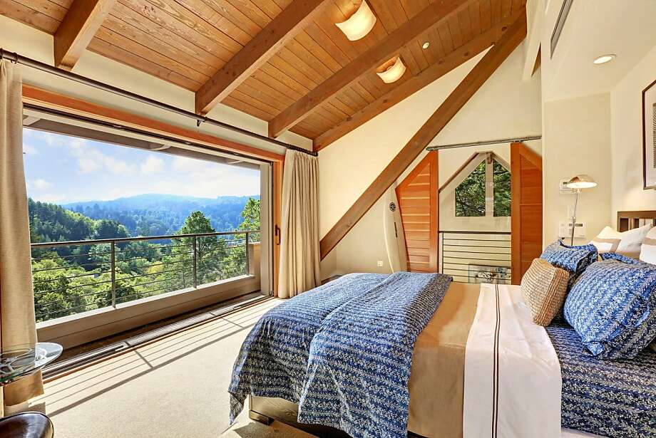 The bedroom suite on the upper level offers pocket doors the open to a view deck. Photo: Jason Wells Photography
