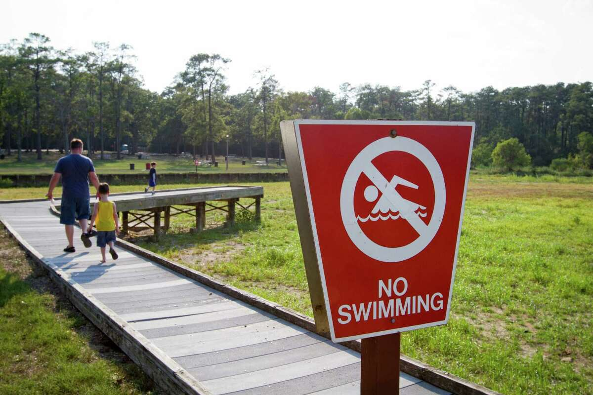 """When Chris Sinclair walked the same dock in August 2011 with sons Gabriel, 5, and Cameron, 7, the """"No Swimming"""" sign seemed unnecessary, as drought conditions had left no water in sight."""