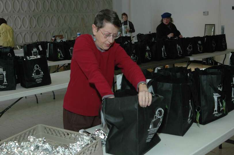 Lois Porter packs meals for the Dec. 11 Dining for Dollars effort, where  volunteers will fan out ac