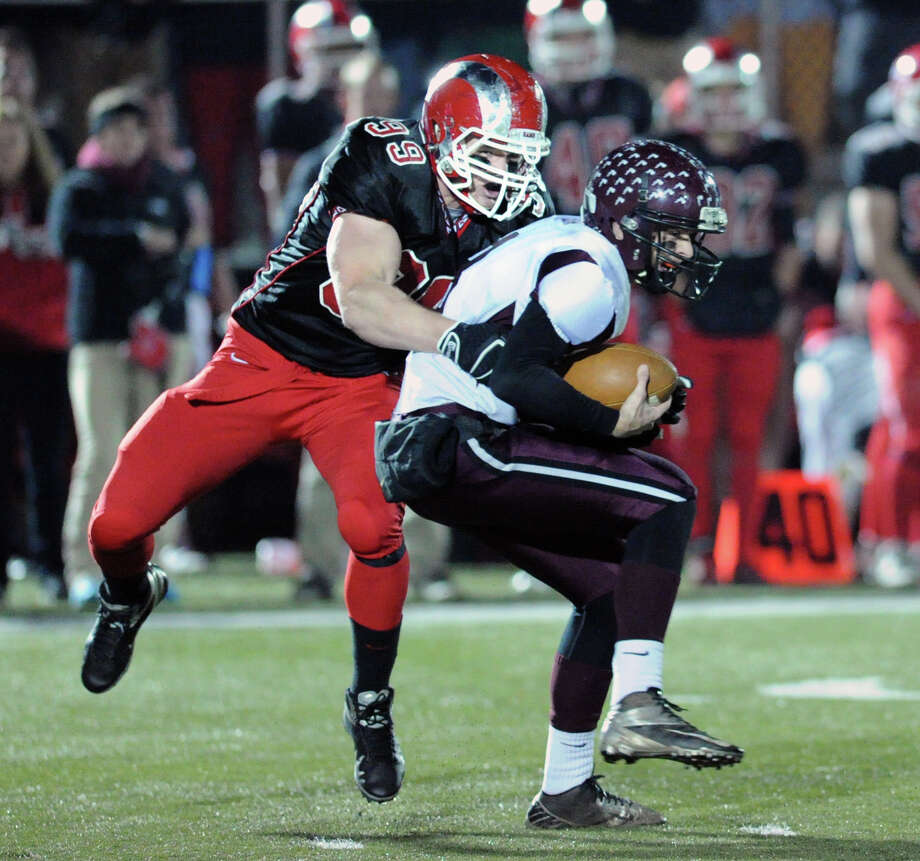 At left, New Canaan's Connor Buck (#99) sacks Farmington quarterback Jeremy Buck during the second quarter of the Class L high school football quarterfinals, New Canaan High School vs. Farmington High School, at New Canaan, Tuesday night, Dec. 3, 2013. Photo: Bob Luckey / Greenwich Time