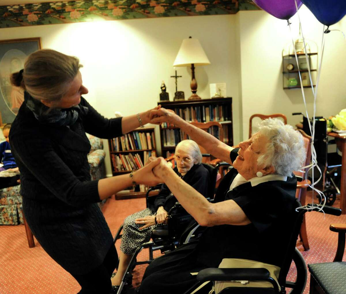 Yoga instructor Mira Lechowicz, left, dances with resident Kay Schottenham on her 103rd birthday before class starts on Wednesday, Nov. 27, 2013, at the Teresian House in Albany, N.Y. (Cindy Schultz / Times Union)