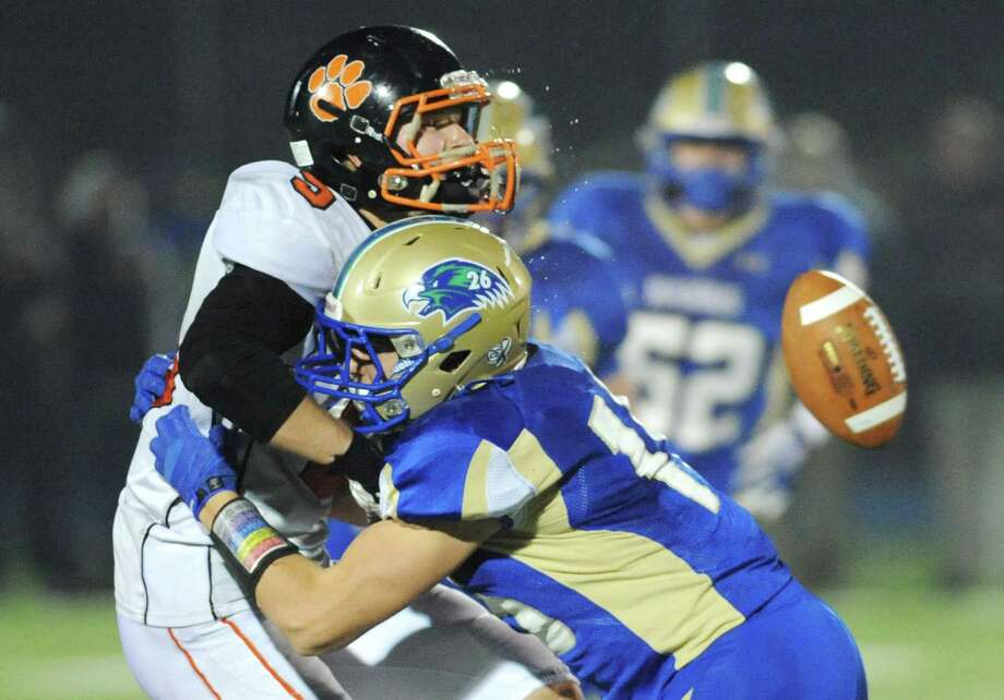 Newtown's Julian Dunn, right, hits Ridgefield receiver Gregory Girolamo in the CIAC Class LL state quarterfinal football game between Ridgefield and Newtown at Newtown High School in Newtown, Conn. on Tuesday, Dec. 3, 2013. Photo: Tyler Sizemore / The News-Times