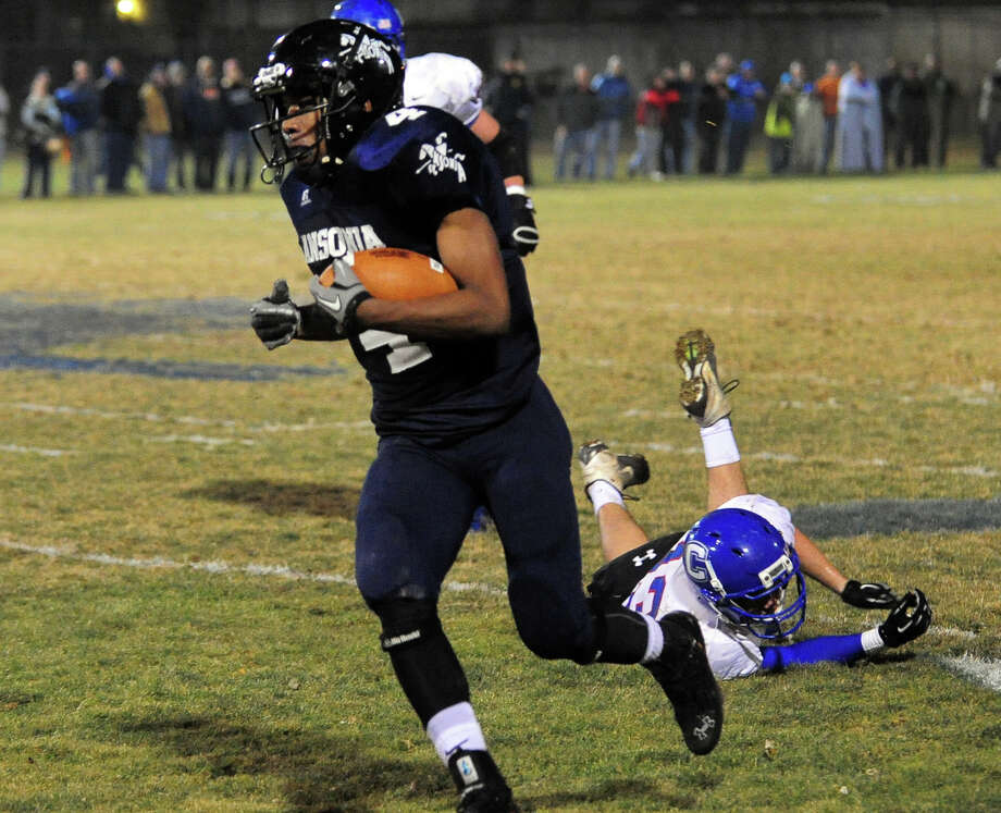 Ansonia's Tajik Bagley looses a Coginchaug man as he carries the ball, during Class football playoff action in Ansonia, Conn. on Tuesday December 3, 2013. Photo: Christian Abraham / Connecticut Post