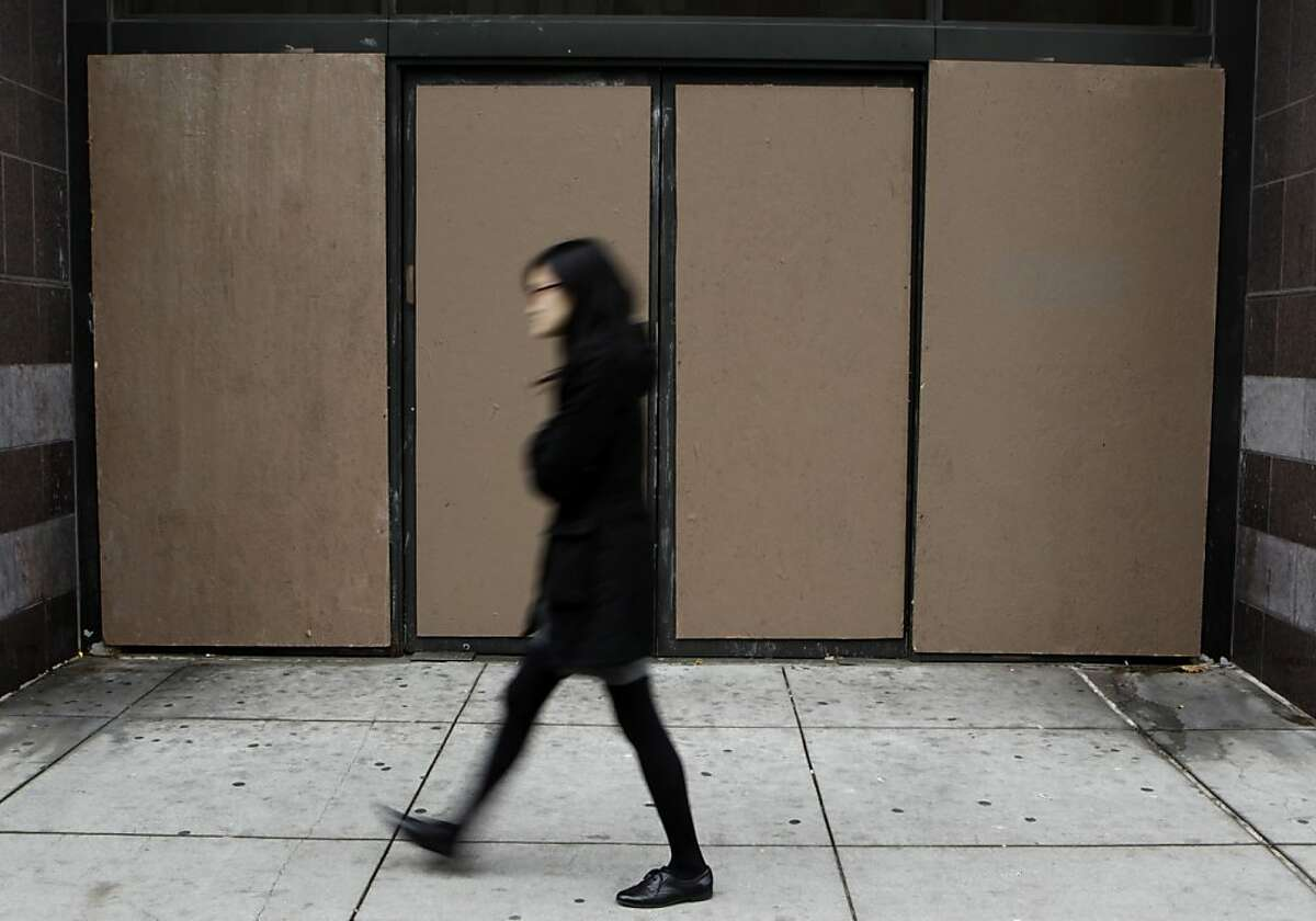 A woman walks past a boarded up entrance to the Sears department store on Telegraph Avenue in Oakland, Calif. on Tuesday, Dec. 3, 2013. The display windows were heavily damaged during demonstrations after the George Zimmerman verdict in July and store management has been slow to replace them claiming it's too expensive.