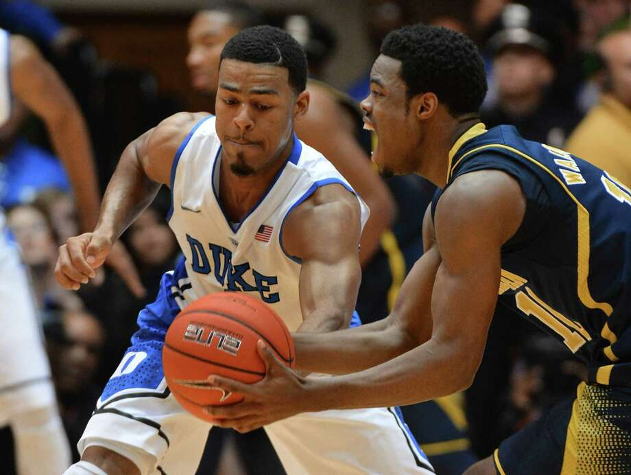 Quinn Cook, left, harassed Michigan's Derrick  Walton Jr. while also leading Duke with 24 points. Photo: Chuck Liddy, MBR / Raleigh News & Observer