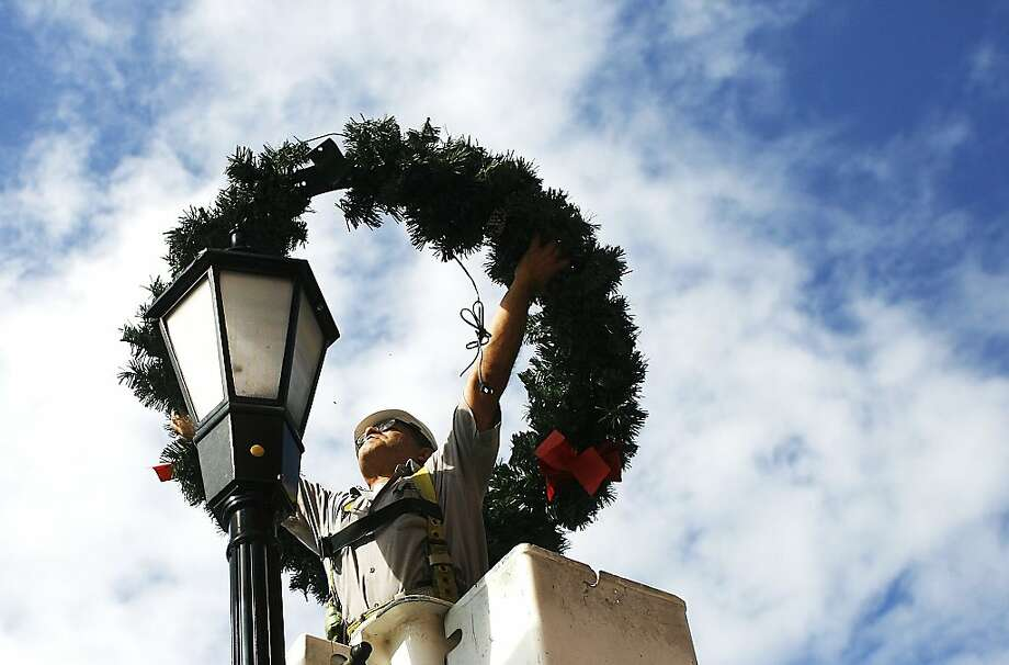 Standing in a bucket truck lift provided by the Hernando County Government public works department Alfred Gonzalez of Spring Hill, an equipment operator with the City of Brooksville's hangs up the final wreath on a street light in downtown Brooksville on Tuesday, Dec. 3, 2013. The City of Brooksville hangs up Christmas decorations atop of street lights in downtown Brooksville on Jefferson Street, Main Street, Howell Avenue, and Dr Martin Luther King Jr Boulevard every year during the week after Thanksgiving says Will Smith the City of Brooksville Utilities Superintendent. (AP Photo/The Tampa Bay Times, Octavio Jones) TAMPA OUT; CITRUS COUNTY OUT; PORT CHARLOTTE OUT; BROOKSVILLE HERNANDO OUT; USA TODAY OUT; MAGS OUT Photo: Jones, Octavio, Associated Press