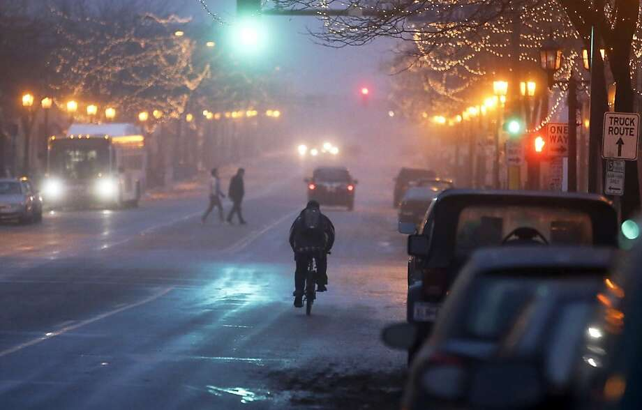 Bicyclists, pedestrians and motorists navigated light fog Tuesday, Dec. 3,  2013, in Minneapolis, Minn., on Nicollet Ave. S. and 26th Street. The second round of winter-like weather is exected to hit late tonight and into Wednesday, leaving behind up to seven inches of snow in some parts of the metro area. (AP Photo/Star Tribune, David Joles) Photo: David Joles, Associated Press