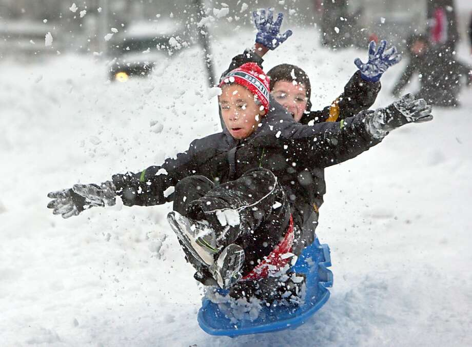 Robert Guthrie, left, 7, and his buddy Eli Glasgow, 8, fly over a snow bump on a track they and their friends made along the sidewalk in Duluth's Central Hillside, Tuesday, Dec. 3, 2013. (AP Photo/Duluth News Tribune, Bob King) Photo: Bob King, Associated Press