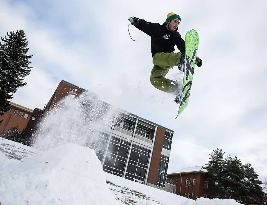 ***STAND ALONE PHOTO***Brent Kroeger, 22, of Pullman, Wash., flies off a jump he constructed on the Washington State University campus behind the Goertzen Communication Addition on Tuesday, Dec. 3, 2013, in Pullman, Wash. (AP Photo/Moscow-Pullman Daily News, Dean Hare) Photo: Dean Hare, Associated Press