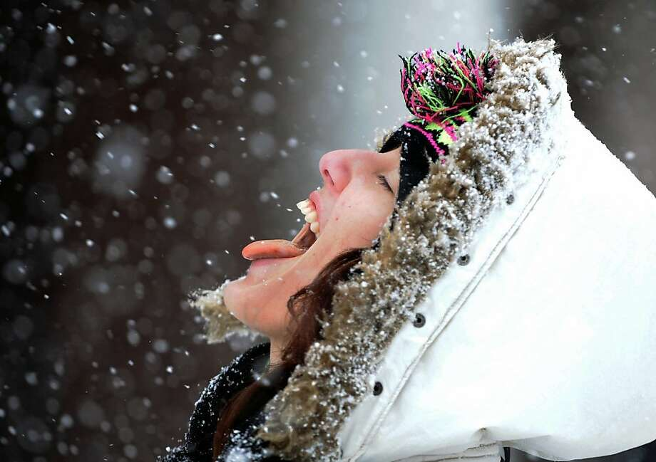 Tasty freeze:University of Nevada student Katrina Avila catches snowflakes on her tongue while walking between 