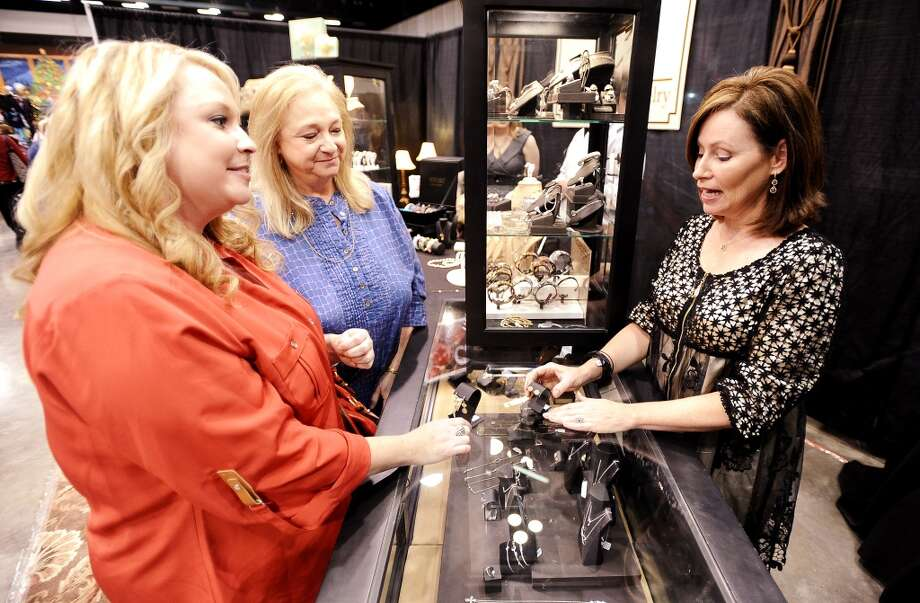 Jenna Shell, left, and her mother Julie Shell, center, talk with Cathy Cook, right, of Cathy Cook Jewely about a set of earrings at the Main Street Market on Thursday, November 29, 2012.  The market, presented by the Junior League of Beaumont, opened Thursday night, continues from 10 a.m. to 7 p.m. Friday and Saturday and 11 a.m. to 5 p.m. Sunday at the Beaumont Civic Center. Friday morning at 10 a.m., guests can take part in the Holiday Happy Hour brunch, which includes a style show and entertainment. On Saturday, Jingle and Mingle with a style show, entertainment, children's workshop and story time. Santa will be available from 10 a.m. to 2 p.m. Saturday for photos with kids. On Sunday, go Cruisin' to Christmas with a style show and entertainment. Throughout the four-day event, vendors will offer jewelry, accessories, clothing, shoes, handbags, maternity items, children's clothing, unique toys, home and holiday décor, food items, wine and more. Admission is $5 for adults and free for children 12 and younger. Photo taken: Randy Edwards/The Enterprise