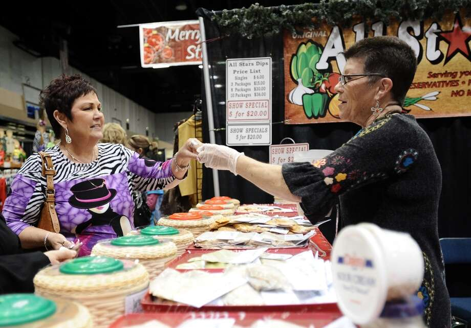 Karen Richard of Bridge City taste dips from All Star Dips during the Main Street Market on Thursday, November 29, 2012.  The market, presented by the Junior League of Beaumont, opened Thursday night, continues from 10 a.m. to 7 p.m. Friday and Saturday and 11 a.m. to 5 p.m. Sunday at the Beaumont Civic Center. Friday morning at 10 a.m., guests can take part in the Holiday Happy Hour brunch, which includes a style show and entertainment. On Saturday, Jingle and Mingle with a style show, entertainment, children's workshop and story time. Santa will be available from 10 a.m. to 2 p.m. Saturday for photos with kids. On Sunday, go Cruisin' to Christmas with a style show and entertainment. Throughout the four-day event, vendors will offer jewelry, accessories, clothing, shoes, handbags, maternity items, children's clothing, unique toys, home and holiday décor, food items, wine and more. Admission is $5 for adults and free for children 12 and younger. Photo taken: Randy Edwards/The Enterprise