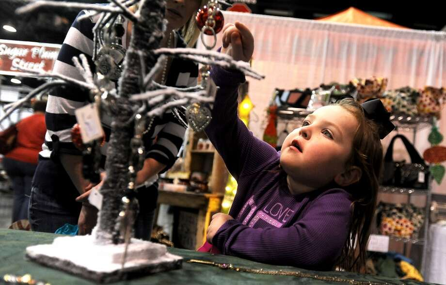 Lakyn Williams is enthralled by shiny baubles on display during the A Very Merry Main Street Market at the Civic Center in Beaumont, Thursday, December 1, 2011. The market, presented by the Junior League of Beaumont, continues from 10:00 am to 9:00 pm Friday and 10:00 am-6:00 pm Saturday. Friday events include aholiday luncheon and style show honoring Michele Smith at 11:00 am. Luncheon tickets are $40.00 and include admission to the market. Events on Saturday include live entertainment and a children's workshop from 10:00 am-2:00 pm with gingerbread houses, reindeer food, Santa photos and letters. Children's workshop tickets are $25.00 and Santa photos are $10.00. Market admission for adults is $5.00. Children under 17 are admitted free. Tammy McKinley/The Enterprise