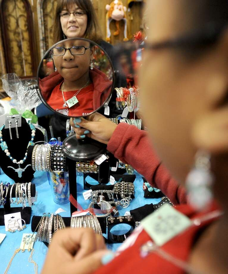 J.J. Pool watches as Mary Duplantier tries on a necklace during the A Very Merry Main Street Market at the Civic Center in Beaumont, Thursday, December 1, 2011. The market, presented by the Junior League of Beaumont, continues from 10:00 am to 9:00 pm Friday and 10:00 am-6:00 pm Saturday. Friday events include aholiday luncheon and style show honoring Michele Smith at 11:00 am. Luncheon tickets are $40.00 and include admission to the market. Events on Saturday include live entertainment and a children's workshop from 10:00 am-2:00 pm with gingerbread houses, reindeer food, Santa photos and letters. Children's workshop tickets are $25.00 and Santa photos are $10.00. Market admission for adults is $5.00. Children under 17 are admitted free. Tammy McKinley/The Enterprise