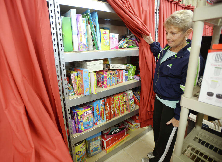 Iva Abel, vice president over Caring Hearts for the Lumberton Civic Women's League, shows off the shelves of Christmas gifts along the back wall of the organization's office Wednesday morning. The donated gifts will be added to packages of food for needy families during the holiday season. The Lumberton Civic Women's League is prepping the Christmas season with bags of food and toys for children. Photo taken Jake Daniels/@JakeD_in_SETX Photo: Jake Daniels / ©2013 The Beaumont Enterprise/Jake Daniels