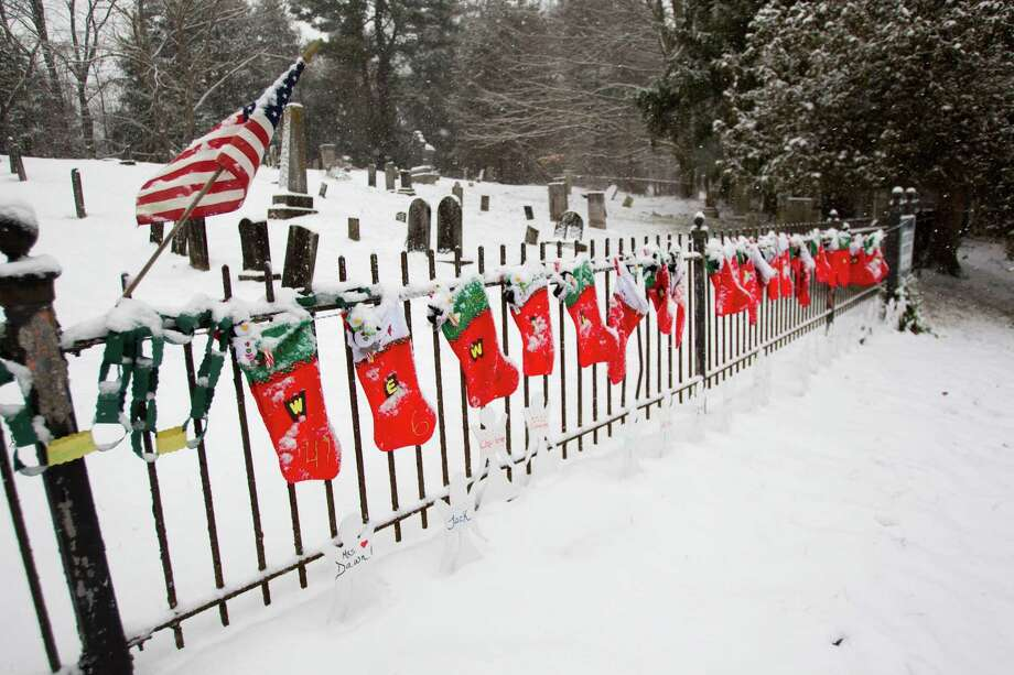 Christmas stockings hang on the fence near Sandy Hook Cemetary near the site of a makeshift memorial for the victims of the Sandy Hook school shooting Saturday, Dec. 29, 2012, in Newtown.  Photo: Brett Coomer, Brett Coomer/Hearst Newspapers / The News-Times