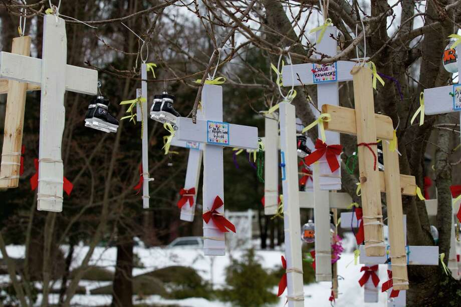 A set of handmade crosses honoring the victims of the Sandy Hook school shooting dangle from a tree Thursday, Dec. 27, 2012, in Newtown.  Photo: Brett Coomer, Brett Coomer/Hearst Newspapers / The News-Times