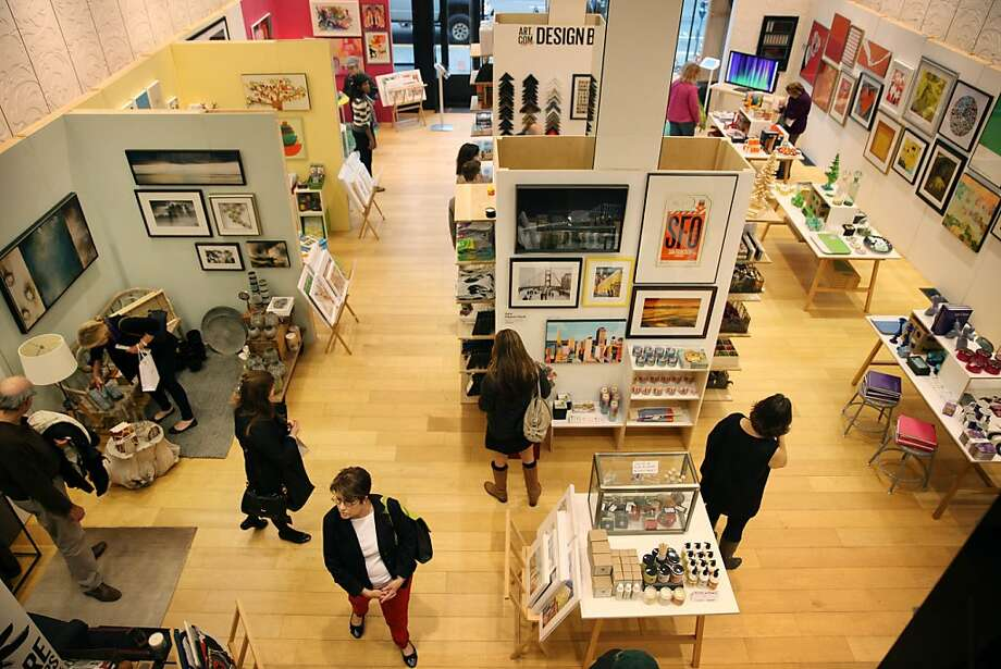 """Shoppers walk through the Art.com store in S.F. The pop-up is a bit like the website, with art grouped in """"rooms"""" - man-cave, mid-century modern living room, playroom - as well as by art selected by tastemakers. Photo: Lea Suzuki, The Chronicle"""