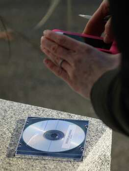 A member of the media photographs a disc containing the recording of 911 calls from Sandy Hook Elementary the morning of the shooting, which were distributed inside the law office of Cohen and Wolf in Danbury, Conn. on Wednesday, Dec. 4, 2013.  The tapes show town responders calmly assuring the callers that help is on its way.  A court ordered the release of the tapes last week, despite the objections of prosecutors, after a legal challenge by The Associated Press. Photo: Tyler Sizemore / The News-Times