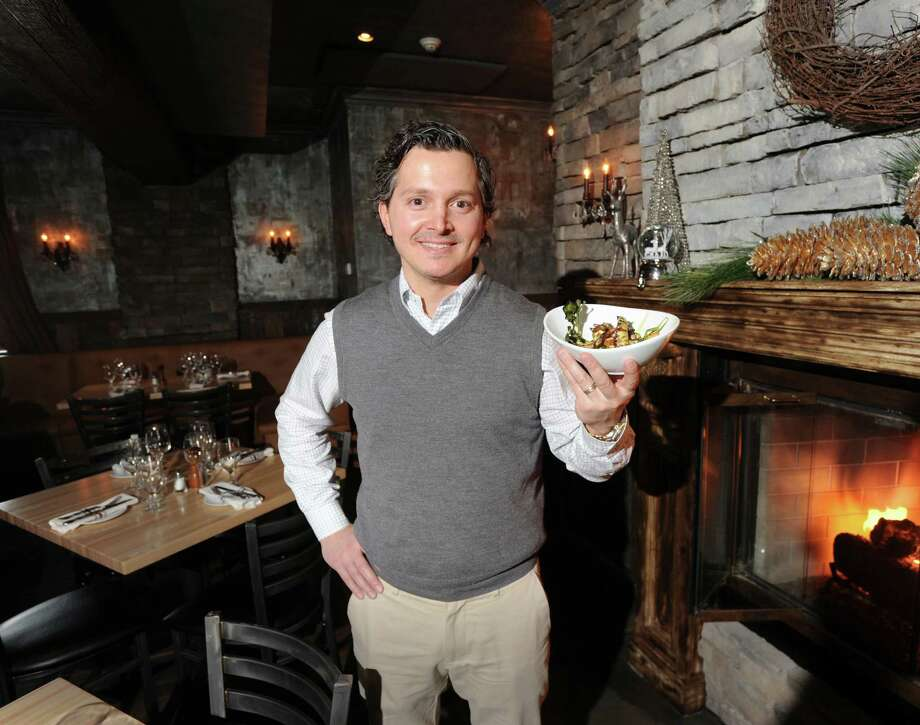 Jimmy Rugova, owner of Char Restaurant, in the main dining room with his restaurant's signature dish, Grilled Spanish Octopus with red watercress, crispy potatoes, garlic confit, and lemon oregano dressing, inside Char at 2 South Water Street , Greenwich, Conn., Wednesday, Dec. 4, 2013. Photo: Bob Luckey / Greenwich Time