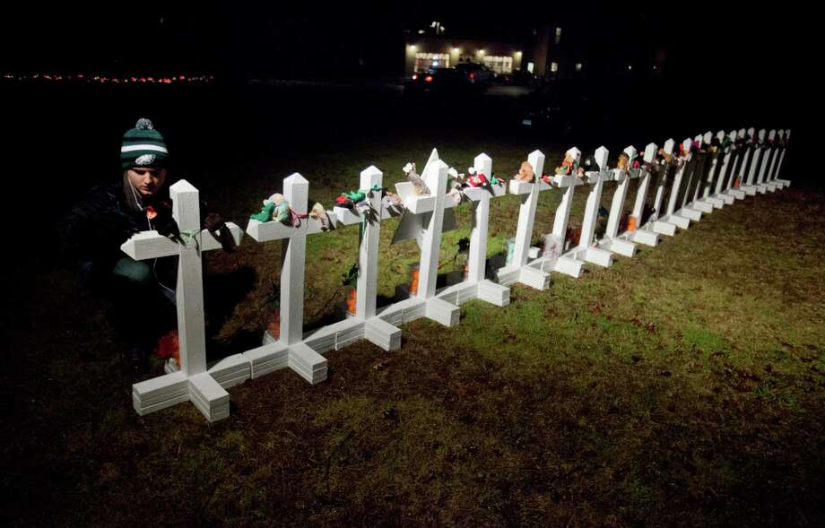Frank Kulick, adjusts a display of wooden crosses, and a Jewish Star of David, representing the victims of the Sandy Hook Elementary School shooting, on his front lawn, Monday, Dec. 17, 2012, in Newtown, Conn. (AP Photo/David Goldman) Photo: David Goldman, Associated Press / AP