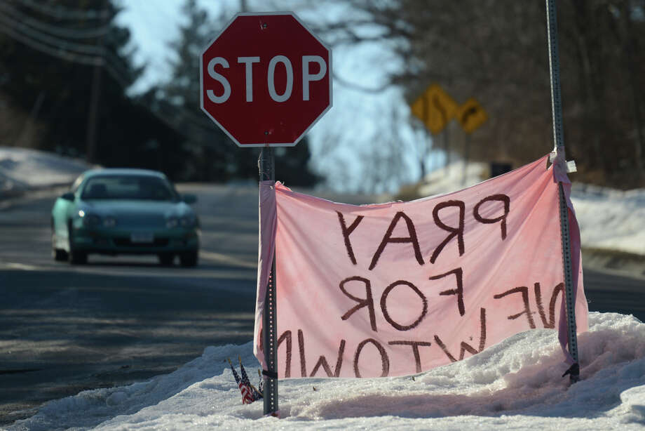 """A car drives by a """"Pray For Newtown"""" flag at the intersection of Main Street and Johnnie Cake Lane in Newtown, Conn. on Thursday, Feb. 21, 2013. Photo: Tyler Sizemore / The News-Times"""
