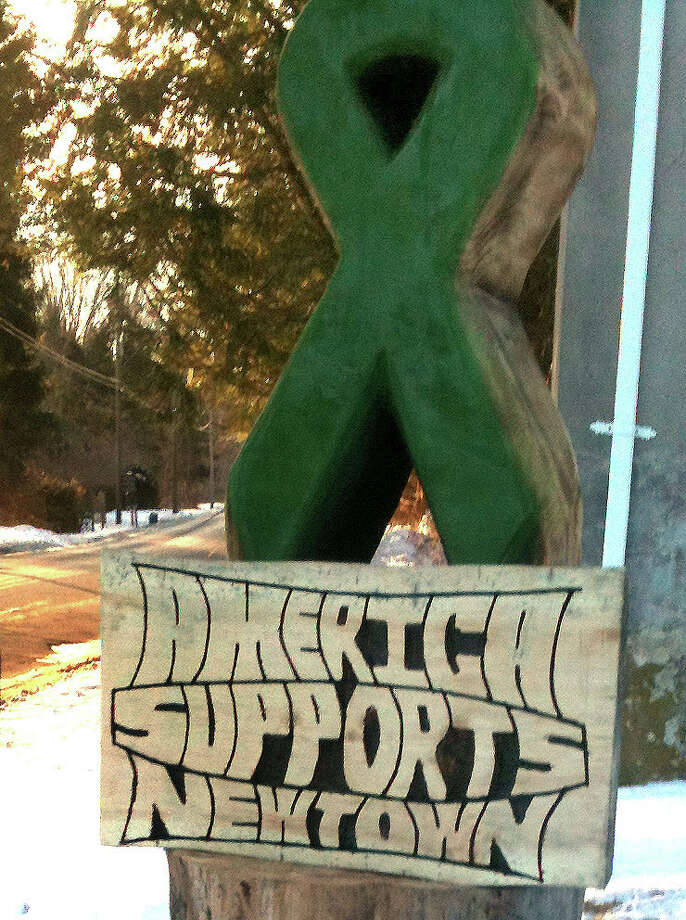 A hand-crafted wooden ribbon stands in front of Jay's Firewood and Tree Service, near the former Chalk Hill School in Monroe, to show support for the Sandy Hook Elementary School students who came to the school from Newtown, Thursday, Jan. 3, 2012. Photo: Nanci Hutson / The News-Times
