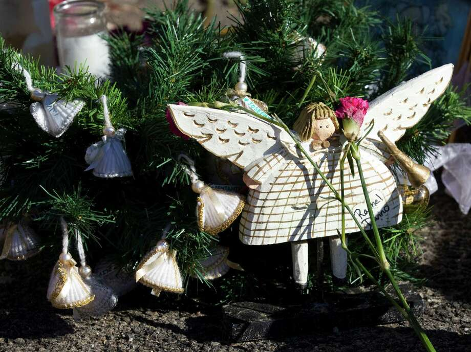 A wooden angel honoring the victims of the Sandy Hook school shooting are part of a makeshift memorial near the school Friday, Dec. 28, 2012, in Newtown.  Photo: Brett Coomer, Brett Coomer/Hearst Newspapers / The News-Times