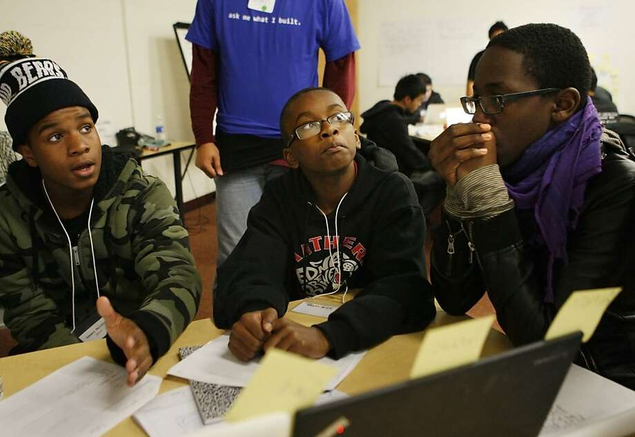 Damani Merritt (left), Tariq Paulding and Pharoah Egbuna discuss their teacher-review app during the Level the Coding Field event. Photo: Raphael Kluzniok, The Chronicle