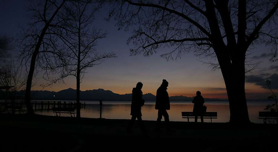 Strollers enjoy the sunset in front of the Alps at Lake Chiemsee in Chieming, Germany. Photo: Matthias Schrader, Associated Press
