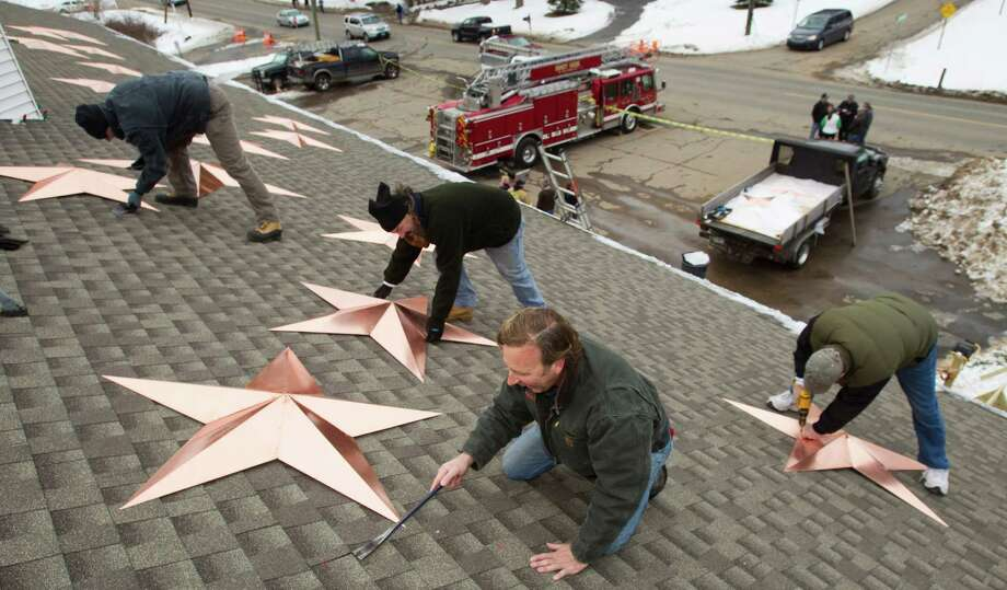 Adrian Szepietowski, from left, Guy Veneruso, Craig Schultz and Len Sabia places stars onto the roof of the Sandy Hook fire house during the installation of 26 stars at the station's roof Tuesday, Jan. 1, 2013, in Newtown, Conn. The stars were made and installed by a group of local contractors, led by Greg Gnandt, to honor the memory of the victims of the Sandy Hook school shooting. Photo: Brett Coomer, Brett Coomer/Hearst Newspapers / The News-Times
