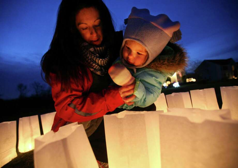 Holly Wheway shows her daughter Esme, 2, luminarias lit in memory of the Sandy Hook Elementary shooting victims in front of her Charter Ridge home in Newtown on Monday, December 24, 2012. Photo: Brian A. Pounds, Connecticut Post / Connecticut Post
