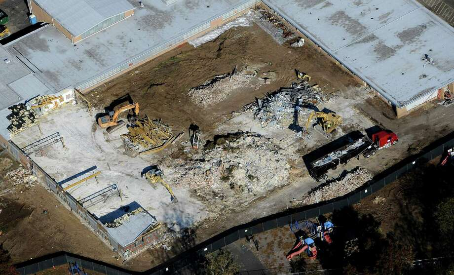 Workers use backhoes to dig through the rubble as the demolition of Sandy Hook Elementary School continues,  Monday, Oct. 28, 2013, in Newtown, Conn.  Workers have begun demolishing the building where a gunman killed 20 children and six adults. The project will take several weeks. Newtown has accepted a $50 million state grant to raze the building and build a new school, expected to open by December 2016. (AP Photo/Jessica Hill) Photo: Jessica Hill, Associated Press / FR125654 AP