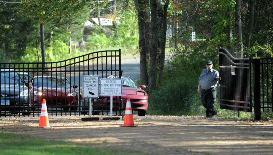 A security guard opens the gate to the old Sandy Hook Elementary School Monday, Oct. 14, 2013, to allow cars to leave the site. Photo: Carol Kaliff / The News-Times