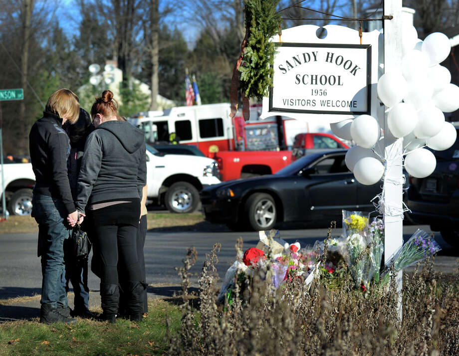 Mourners hold hands in a circle near a memorial of flowers, notes and stuffed animals left next to a sign for the Sandy Hook Elementary Saturday, Dec. 15, 2012 in Newtown, Conn. Photo: Carol Kaliff / The News-Times