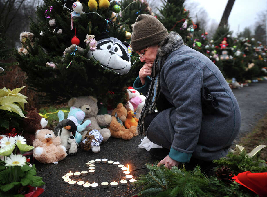 Tracy Kirk of Southbury lights candles in the shape of a heart outside the entrance to Sandy Hook Elementary School in Newtown on Sunday, December 16, 2012. Photo: Brian A. Pounds / Connecticut Post