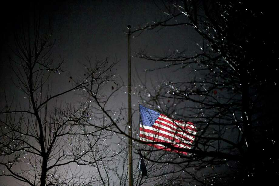 A U.S. flag flies at half staff outside the  Newtown High School before President Barack Obama is scheduled to attend a memorial for the victims of the Sandy Hook Elementary School shooting, Sunday, Dec. 16, 2012, in Newtown, Conn. A gunman walked into Sandy Hook Elementary School in Newtown Friday and opened fire, killing 26 people, including 20 children. (AP Photo/David Goldman) Photo: AP