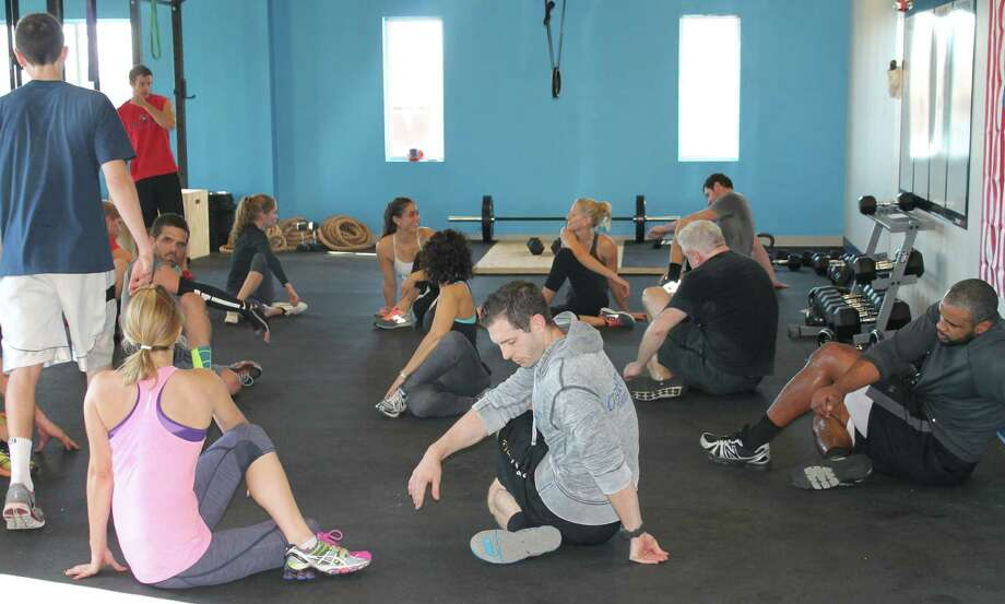 One of the principles of CrossFit training is for clients to work in a supportive and less competitive group envirorment than in some gyms. Photo: Contributed Photo / Fairfield Citizen