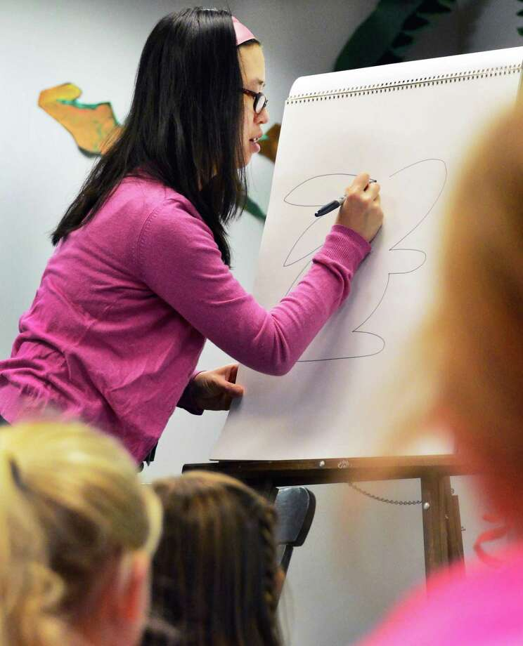 Award-winning author and illustrator Grace Lin draws some of her book characters for Saint Gregory's School students  Wednesday Dec. 4, 2013, in Colonie, NY.  (John Carl D'Annibale / Times Union) Photo: John Carl D'Annibale / 00024668A