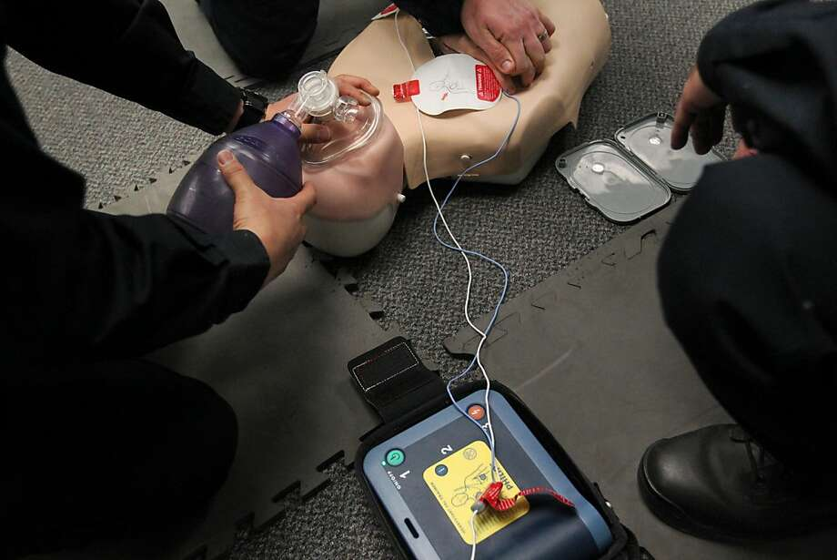 Officers Warren Lee, Jordan King and Stacy Youngblood demonstrate how to use a defibrillator. Photo: Leah Millis, The Chronicle