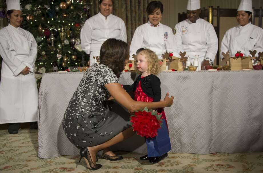 First Lady Michelle Obama hugs two-year-old Ashtyn Gardner during the White House Christmas decorations viewing at the White House in Washington, DC, December 4, 2013. Photo: JIM WATSON, AFP/Getty Images