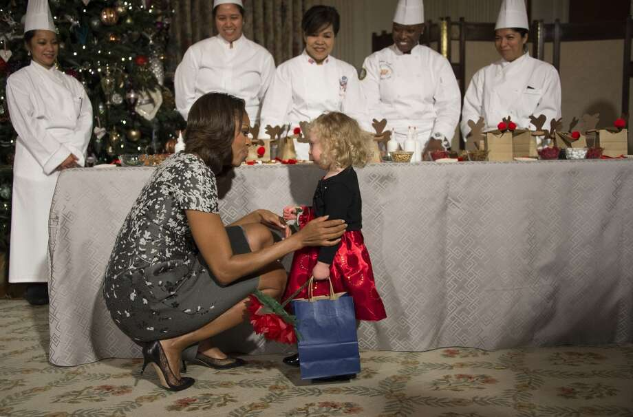 First Lady Michelle Obama speaks with two-year-old Ashtyn Gardner during the White House Christmas decorations viewing at the White House in Washington, DC, December 4, 2013. Photo: JIM WATSON, AFP/Getty Images